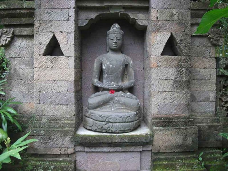 A statue of budda holding the famous red hibiscus