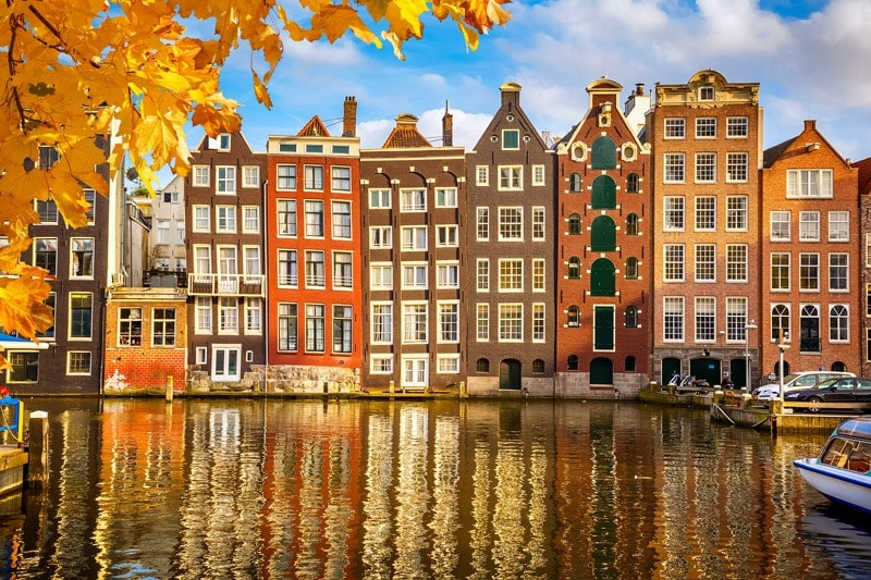 houses reflected in the canal in amsterdam, the netherlands